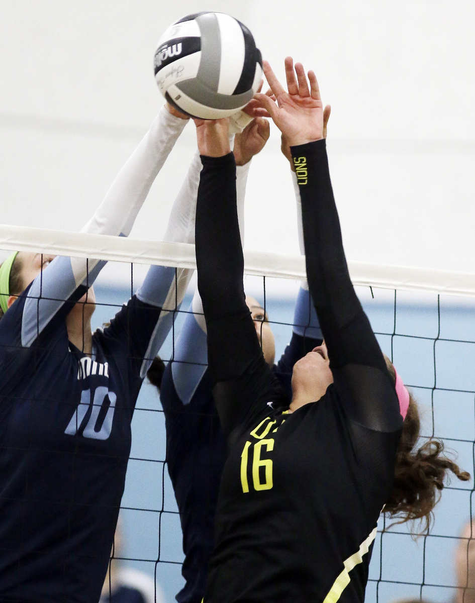 Anne  Debbane (16) Ursuline and  Mount Notre Dame's Dani  Szczepanski meet at the net  during the their volleyball game,