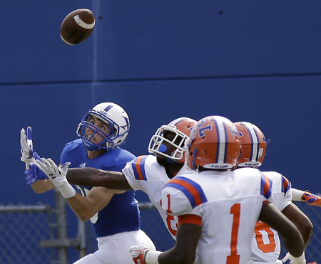 St. Xavier's Brian Johnston tries to catch a pass in front of East St. Louis defenders, during their football game