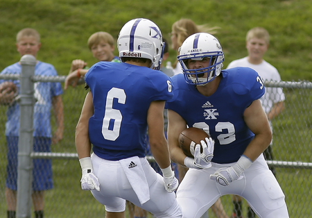 St. Xavier's Sean Prophit (32) celebrates with teamate Sam	 Ankenbauer after scoring a touchdown during the Bombers football game against East St. Louis,